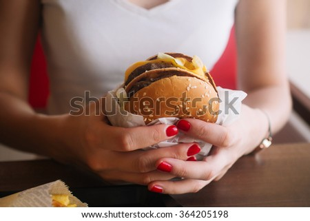 Girl holding a Burger. Teen girl with a delicious burger. Hand holding a tasty fast food cheeseburger. The concept of fast food. Tasty unhealthy Burger sandwich in hands, ready to eat - stock photo