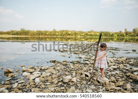 girl holding a dry branch of the river