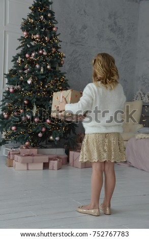 girl holding a gift box near the Christmas tree, back view