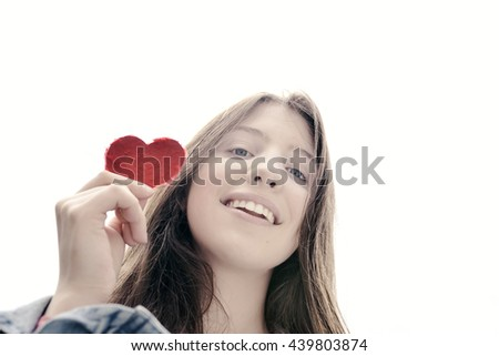 Girl holding a heart of paper - symbol for love  - stock photo