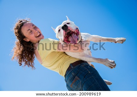 Girl holding a huge dog breed Staffordshire Terrier