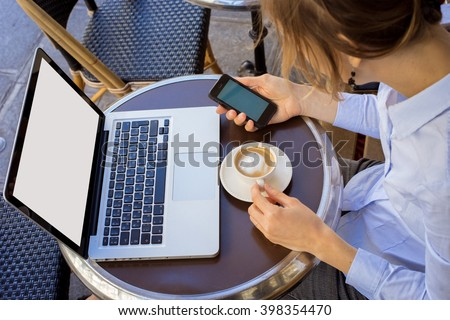 girl holding a mobile phone. Computer and coffee on the table in the cafe.  - stock photo