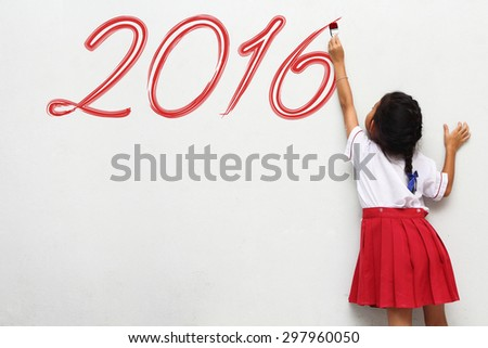 Girl holding a paint brush painting happy new year 2016 on a white wall background - stock photo