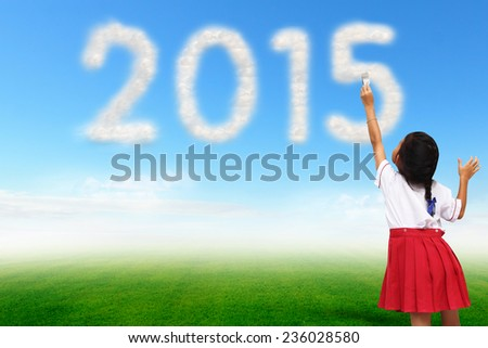 Girl holding a paint brush painting on cloud in blue sky over meadow with a shaped of number 2015 new year - stock photo