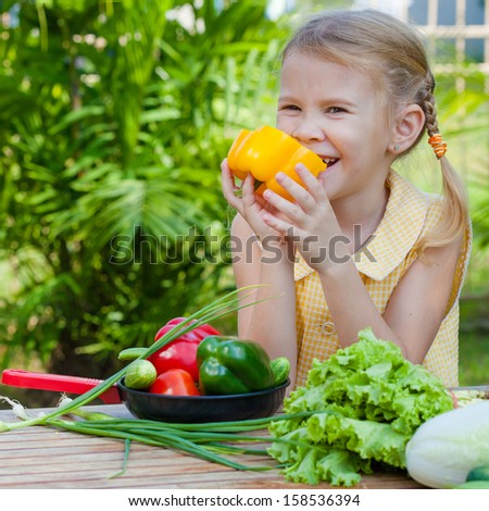 girl holding a pan of vegetables (cucumber, pepper, tomato, onion)