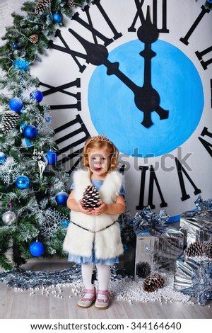 Girl holding a pine cone. The clock in the background show five minutes to midnight. Christmas Eve. New Year. Holiday and fun. Merry Christmas. 2017 - stock photo