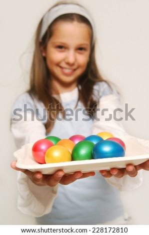 Girl holding a plate with easter eggs - stock photo