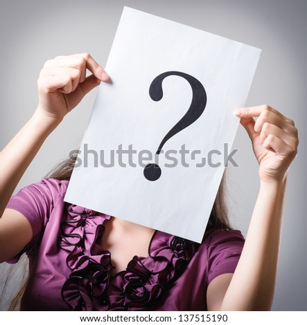 Girl holding a question mark - stock photo