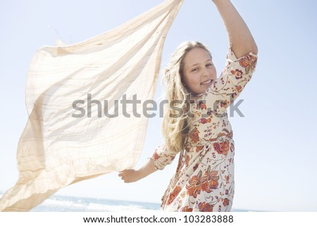 Girl holding a sarong in the air blowing in the sea breeze. - stock photo
