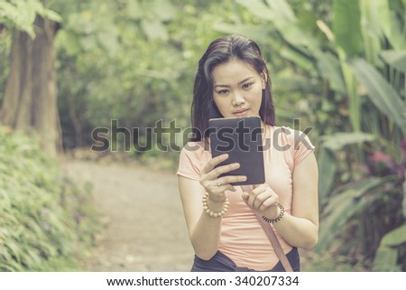 Girl holding a tablet computer outdoor park