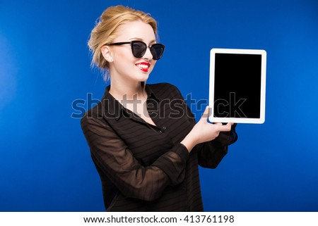 girl holding a tablet in the hands on a blue background - stock photo