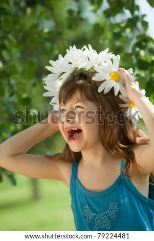 girl holding a wreath of daisies and fun laughs - stock photo