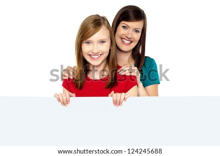 Girl holding ad board with her mother behind her. Mother resting hands on daughter. - stock photo
