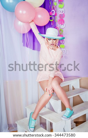 Girl holding air balloons. Attractive girl with makeup in the style of pop art. The girl in the hat. Pink hair. Vintage fashion. Holiday concept.