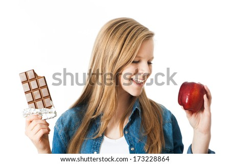 Girl holding an apple and a chocolate in her hands - stock photo
