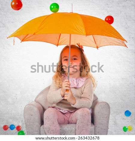 Girl holding an umbrella droping colorful balls - stock photo