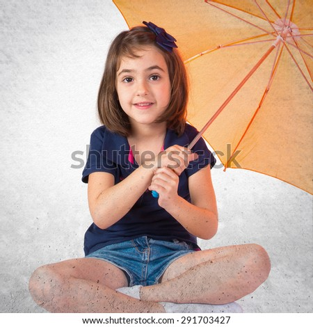 Girl holding an umbrella over grey background
