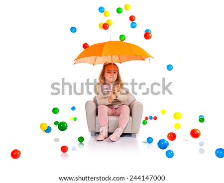 Girl holding an umbrella while droping colorful balls - stock photo