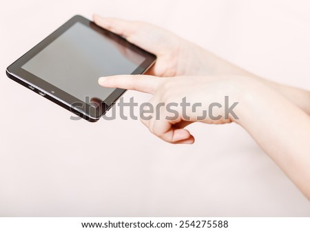 girl holding and clicking tablet-pc screen on pink background - stock photo