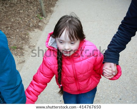 Girl holding arms of parents on a walk - stock photo