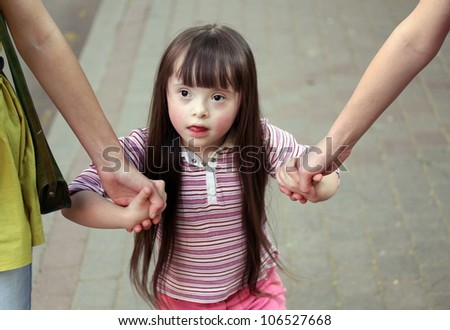 Girl holding arms of the sisters on a walk . - stock photo