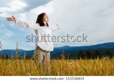 Girl holding arms up against blue sky - stock photo