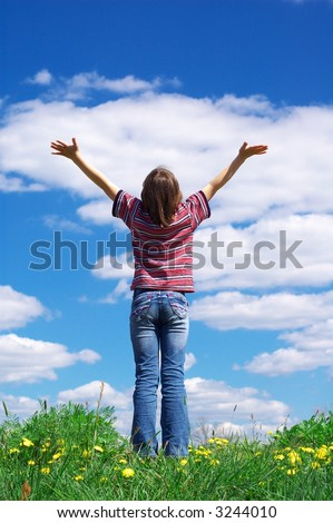 girl holding arms up in praise against blue sky