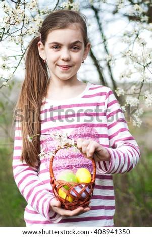 Girl holding basket full of colorful easter eggs - stock photo