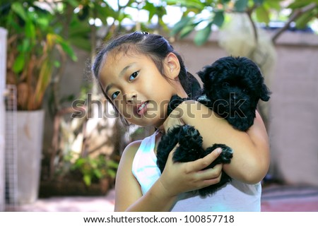girl holding black puppy - stock photo