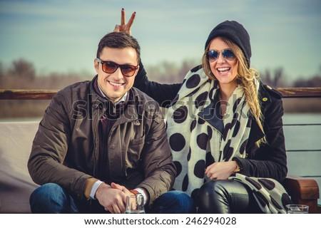 Girl holding bunny ears to her boyfriend - stock photo