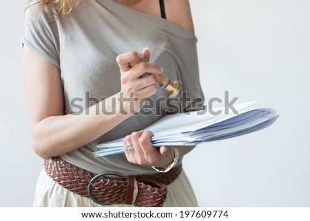 girl holding business documents, folders and ink stamp on white background - stock photo