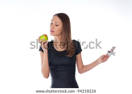 girl holding chocolate and apple in the hands on a white - stock photo
