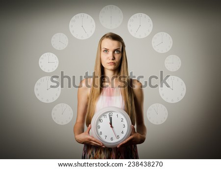 Girl holding clock in her hands. Time concept. Several minutes to twelve. - stock photo