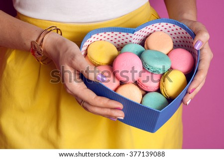 Girl holding colorful french macaroons in box in hands - stock photo
