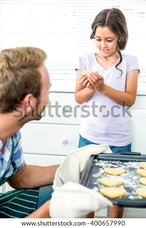 Girl holding cookie while father looking at her and holding tray in kitchen - stock photo