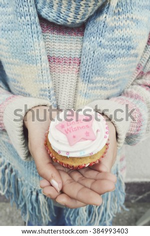 girl holding cupcakes decorated  with cream and heart, Valentine's Day