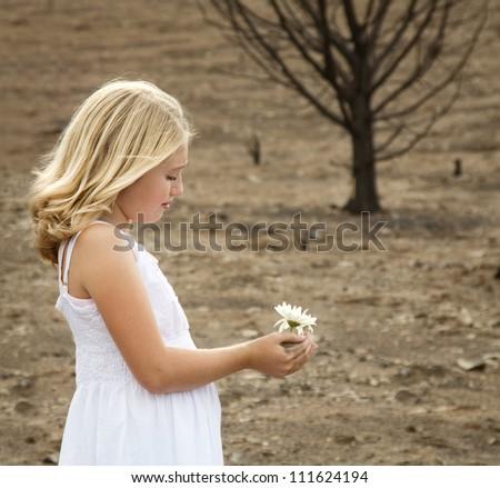 Girl holding flower in barren burnt landscape - stock photo