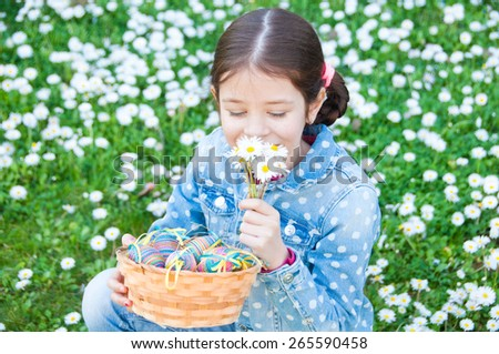 Girl holding flowers and a basket with easter eggs - stock photo