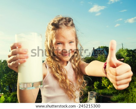 Girl holding glass with milk. Happy child at summer - stock photo