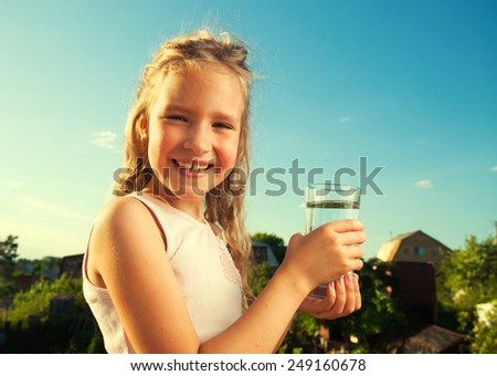 Girl holding glass with water. Happy child at summer - stock photo