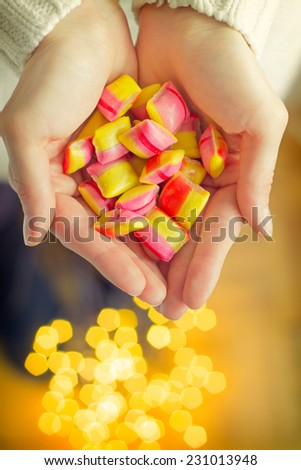 Girl holding hands with candies, Christmas lights on the floor - Selective Focus, Shallow DOF - small grain added - stock photo
