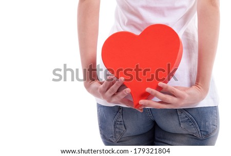 Girl holding heart behind back