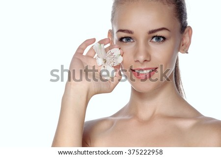 Girl holding in her hand a white lily, putting her cheek and smiling. Beauty concept - girl with well-groomed skin.