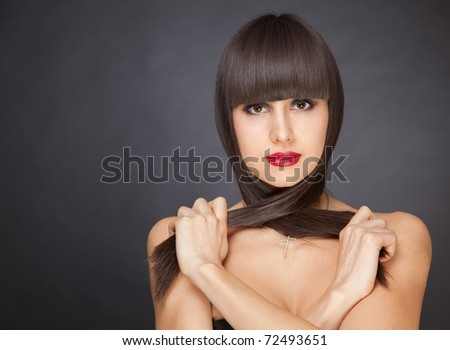 Girl holding long hair, portrait studio isolated shot - stock photo