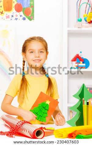 Girl holding New Year card with Xmas tree