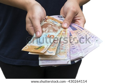 girl holding New Zealand banknote.