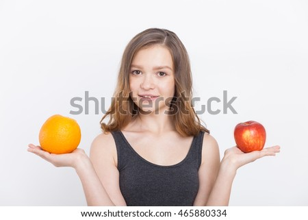 Girl holding orange and apple and looking at camera smiling. Concept of right nutrition choices. Portrait. Isolated