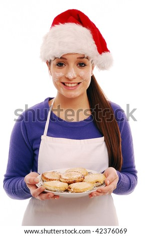 Girl holding plate of freshly cooked mince pies on white background - stock photo