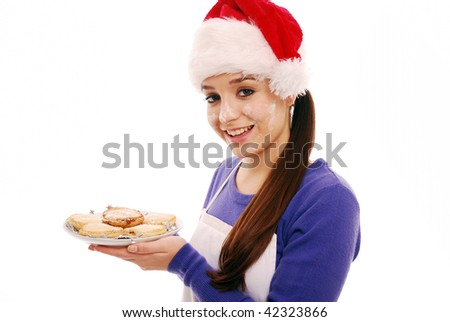 Girl holding plate of mince pies with flour on her face - stock photo