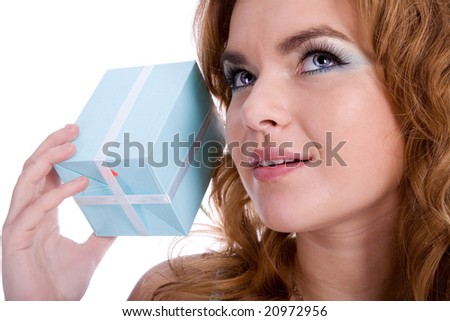 Girl holding present and guessing what inside - stock photo